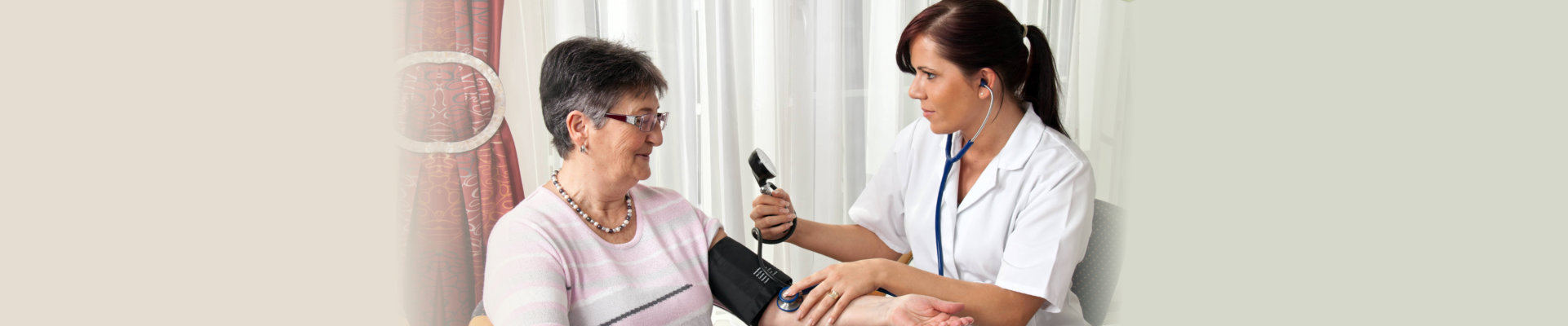 nurse checking her patient's blood pressure
